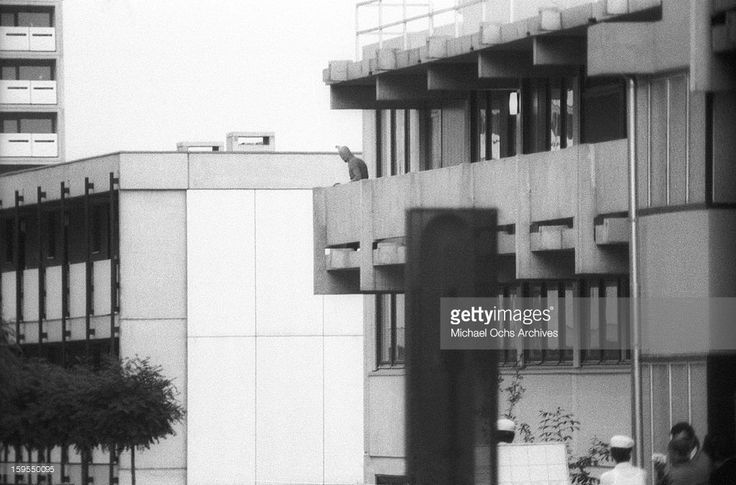 A member of the Black September Organization (a terrorist group afilliated with the Palestine Liberation Organization) stands on the balcony of the Israili Olympic team quarters, where the group are holding 9 surviving Israeli hostages, on September 5, 1972 in Munich, West Germany.