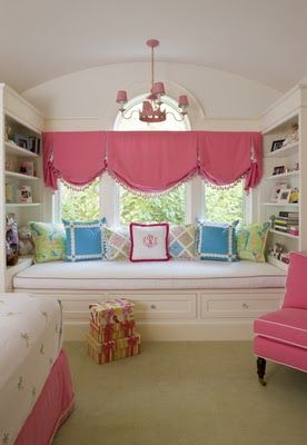 I like the style of the valance, the window seat, & the cheerful colors, but I think I would have done a different treatment- this looks a bit low. I would put white wood blinds in the windows, including the arch if sun was a problem, & have an arched casual swag hung from a bracket above the arch, coming down on either side with tiebacks or holdbacks. I think it would highlight the pretty window better.