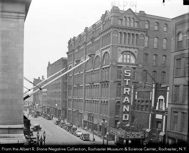 "In this view of St. Paul Street, the vertical sign identifying the Strand Theatre occupies a prominent place at the right. On the side of the marquee, the letters read, ""Hear Barthelmess talk & sing. Drag: a great picture"". According to the Internet Movie Data Base (IMDB), Richard Barthelmess played the lead in the motion picture Drag, which was released in 1929. It was in black-and-white, and was released in both monaural and silent versions. Rochester NY"