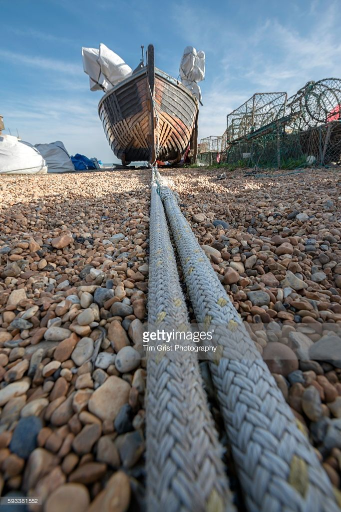 Low angle detail shot of mooring rope and a wooden fishing boat resting on a pebble beach surrounded by fishing nets and pots.