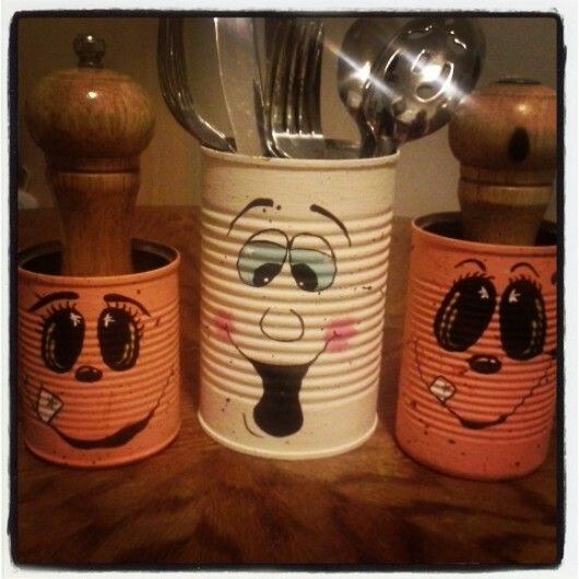 Halloween utensil holder ghost and pumpkins made from tin cans.