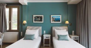 GREEK STYLE VILLAS - Twin bedroom with a green feature wall.