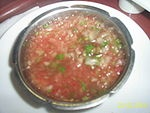 Pebre[1] is a Chilean condiment made of coriander, chopped onion, olive oil, garlic and ground or pureed spicy aji peppers. Pebre is most commonly spooned on meat, usually from a barbecue. If you add chopped tomatoes it is called chancho en piedra.