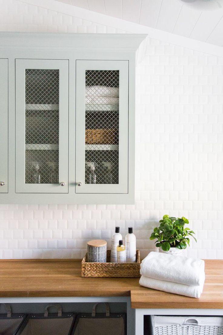 Mint green cabinets in laundry room with white square subway tile