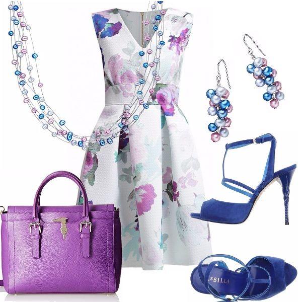 Un outfit semplice ma ricercato negli abbinamenti. Abito in un delicata fantasia floreale nei toni del viola, lilla, blu azzurro: scollo a V senza maniche…