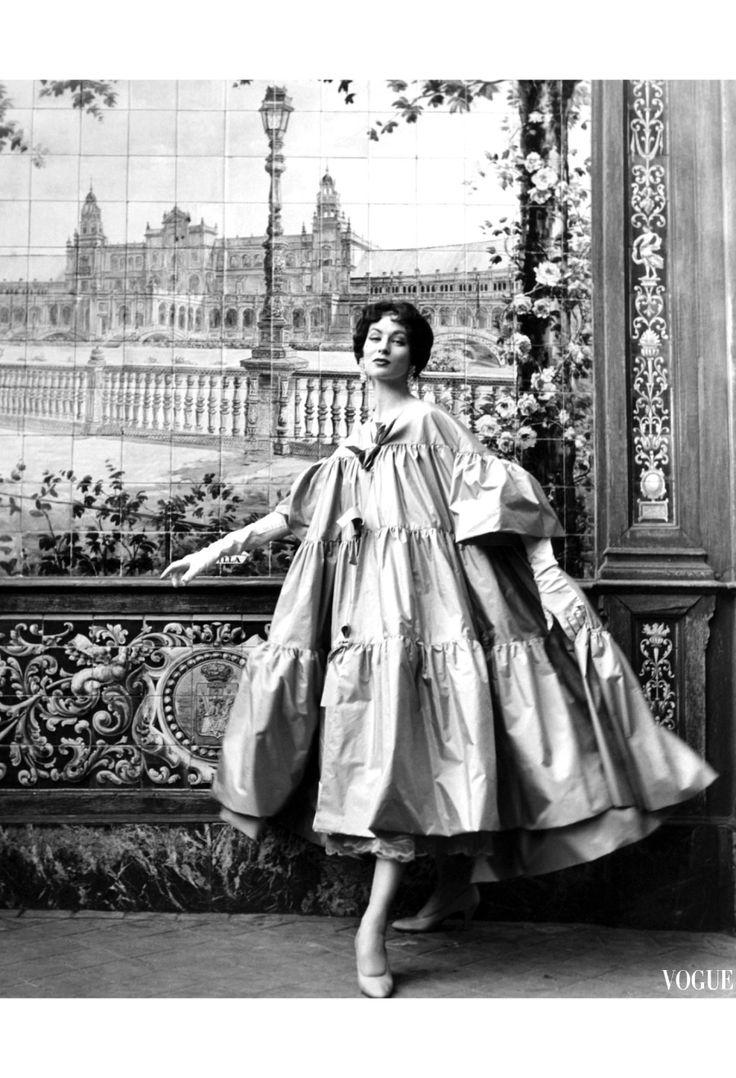 Model Suzy Parker wears a voluminous bow-tied coat by Pertegaz iVogue March 15, 1954 © Henry Clarke