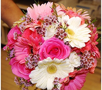 Coral colored gerber daisies matched with light pink and white gerbers, pink waxflowers along with coral and hot pink colored roses.