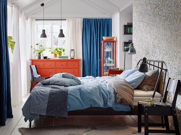 Dormitorio mediano con una cama de matrimonio de acero gris oscuro, ropa de cama de color gris y azul claro, y una cómoda roja con cuatro cajones pequeños y cuatro grandes.