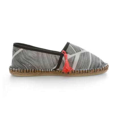 Une espadrille noire et blanche, rehaussée d'un pompon rose sur le pied droit. Le pompon est amovible et interchangeable !