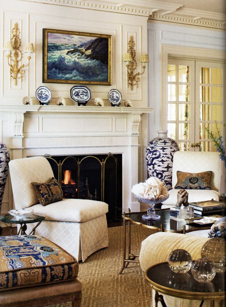 beautiful living room decor with carved wood Italian Adam style sconces above the fireplace mantel; gold leaf sconces