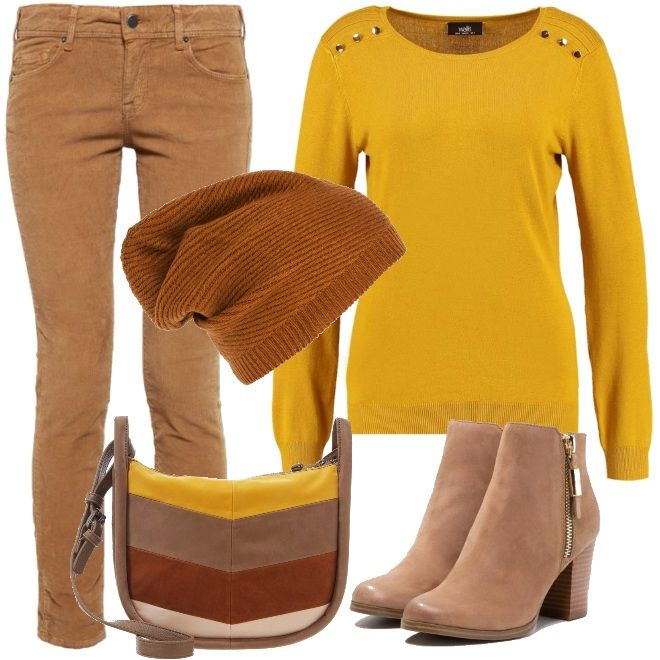 Maglione giallo ocra a manica lunga con bottoncini dorati sul davanti, pantalone camel slim fit a vita bassa con tasche posteriori, tronchetti in pelle con cerniera laterale. Per gli accessori berretto color cognac e shopping bag a tracolla.