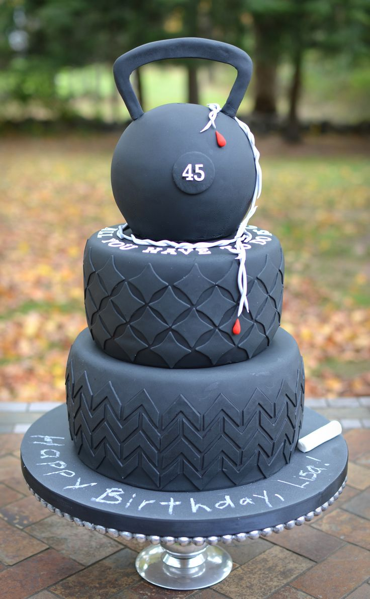 A trainer's cake, complete with tires, chalkboard, kettlebell and barbed wire.