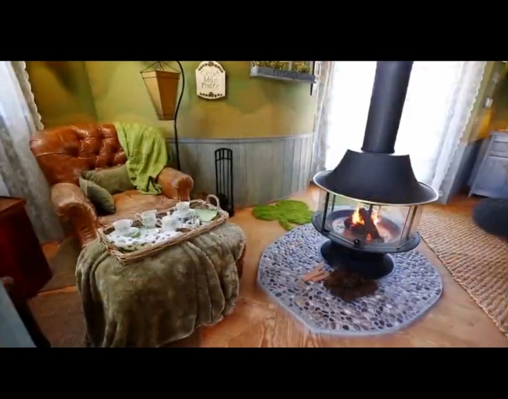 treehouse masters irish cottage leather chair sittingreading area beside central fireplace - Treehouse Masters Irish Cottage