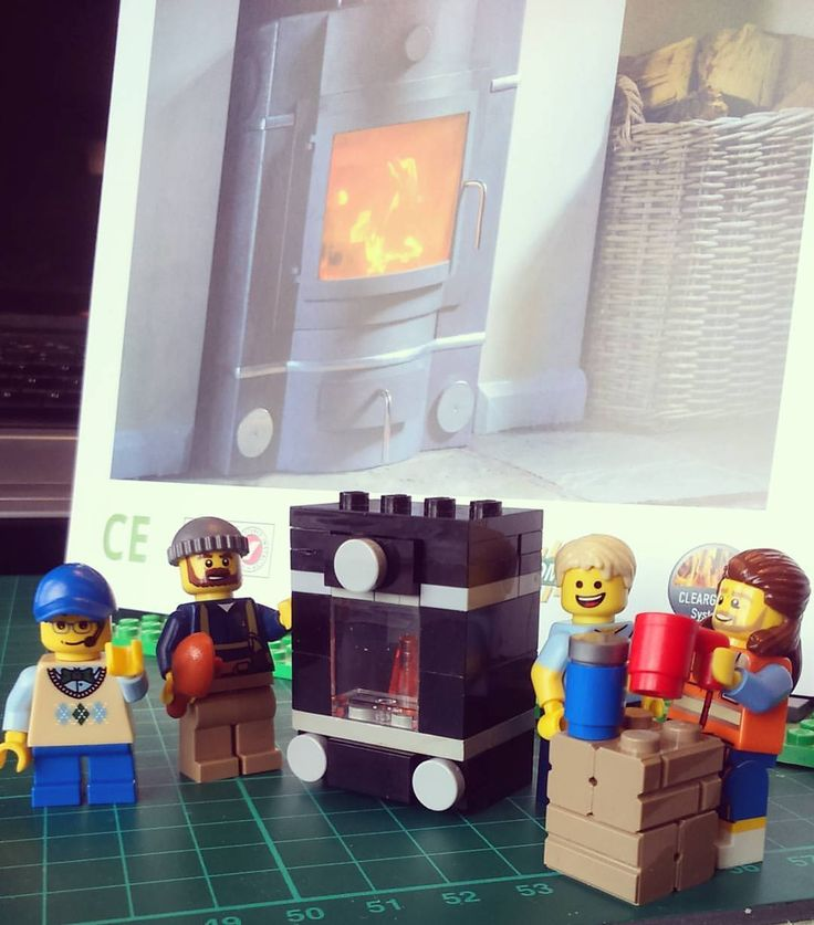 """My first """"proper"""" Lego woodburning stove, based on the Ecco Stove E678 (pictured in the background).  The BTSE team has developed (from left to right): myself, Brandon, Dan and Tony.  Tony loves coffee, so will now always be pictured with a mug."""