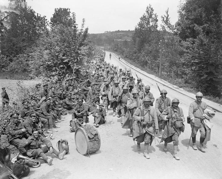 The Third Battle of the Aisne. French infantry coming back through Passy-sur-Marne pass British regimental band resting by the roadside, 29 May 1918.