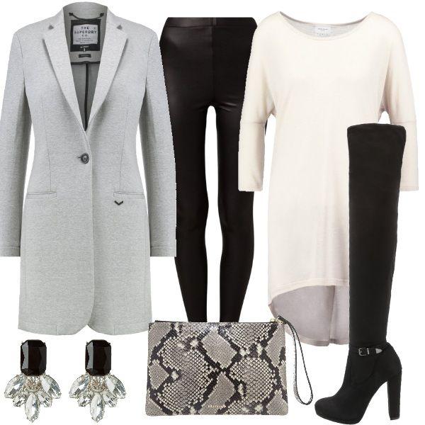 Un outfit glamur, composto da maxi maglia abbinata a leggings neri e stivali sopra al ginocchio con fibbia alla caviglia. Completano il look il blazer grigio, la pochette animalier e gli orecchini a lobo che donano luce.