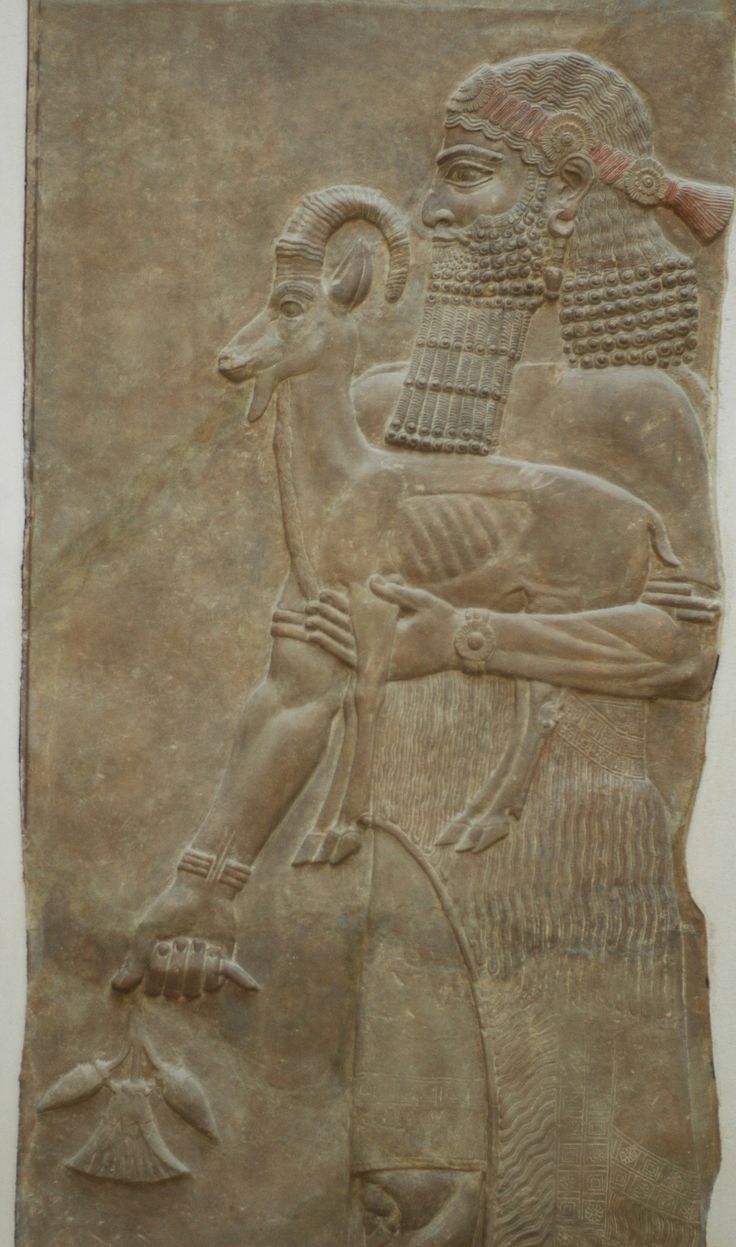 Goat beard & Santa Claus / Person holding an ibex and a poppy flower. Low-relief from the m wall of king Sargon II's palace at Dur Sharrukin in Assyria (now Khorsabad in Iraq), c. 713–716 BC. From Paul-Émile Botta's excavations in 1843–1844.
