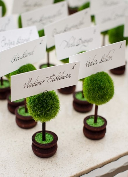 Mini topiary escort cards. Maybe white containers to bring in something a little lighter? Calligraphy to match invites.