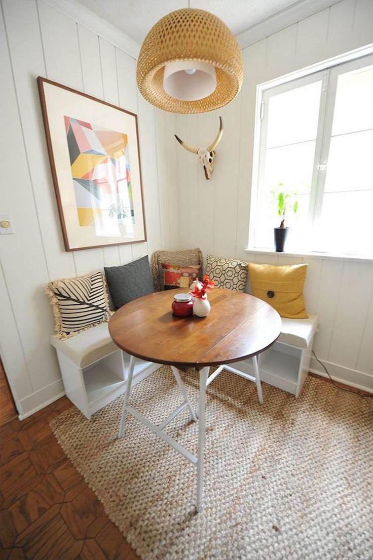 banquette d'angle avec compartiments de rangement, une table ronde en bois et blanc et revêtement mural en bois blanchi