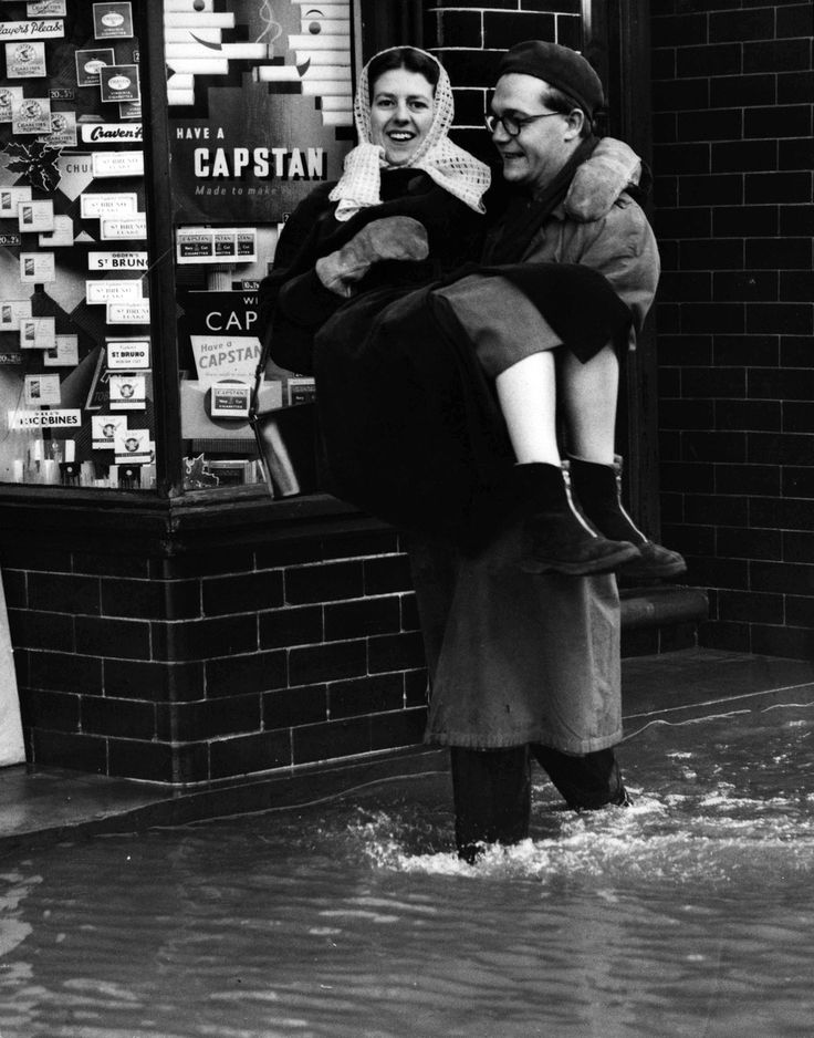 17th January 1955. A woman is carried down the street by a helpful gentleman after a severe flood in Tonbridge, Kent. The flooding was cause...
