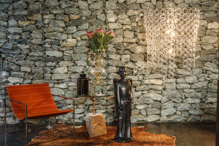 Acrylic Surilight glowing against a Gabion stone wall, contemporary African inspired interior with leather sling chair.