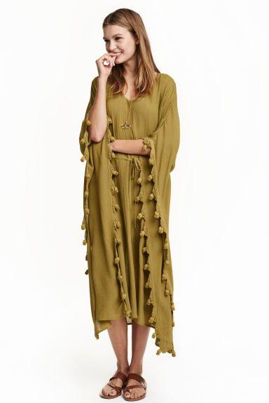 Платье-кафтан: Платье-кафтан длиной до икры из жатой, тканой вискозы с декоративной окантовкой. На платье треугольный вырез и талия на кулиске. Разрезы по бокам. Без подкладки.