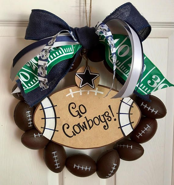 Hey football fans! This Cowboys wreath is perfect for your front door, back door, bedroom, classroom or office. It can be made for any team, using any colors. The wreath is made with foam footballs. A big wired burlap bow is accented with blue, silver, white and Cowboys ribbon of various widths. A hand-painted, football shaped sign and round wooden circle hang from the top of the wreath. The sign reads, Go Cowboys, in blue and white. It can be changed to say anything youd like.. a team name…