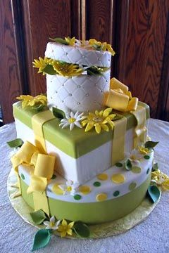 Three tier, green, white and yellow theme gift box wedding cake design, decorated with white and yellow handmade daisies, yellow and pink polka dots and yellow fondant ribbons. From www.butterflycakes.com