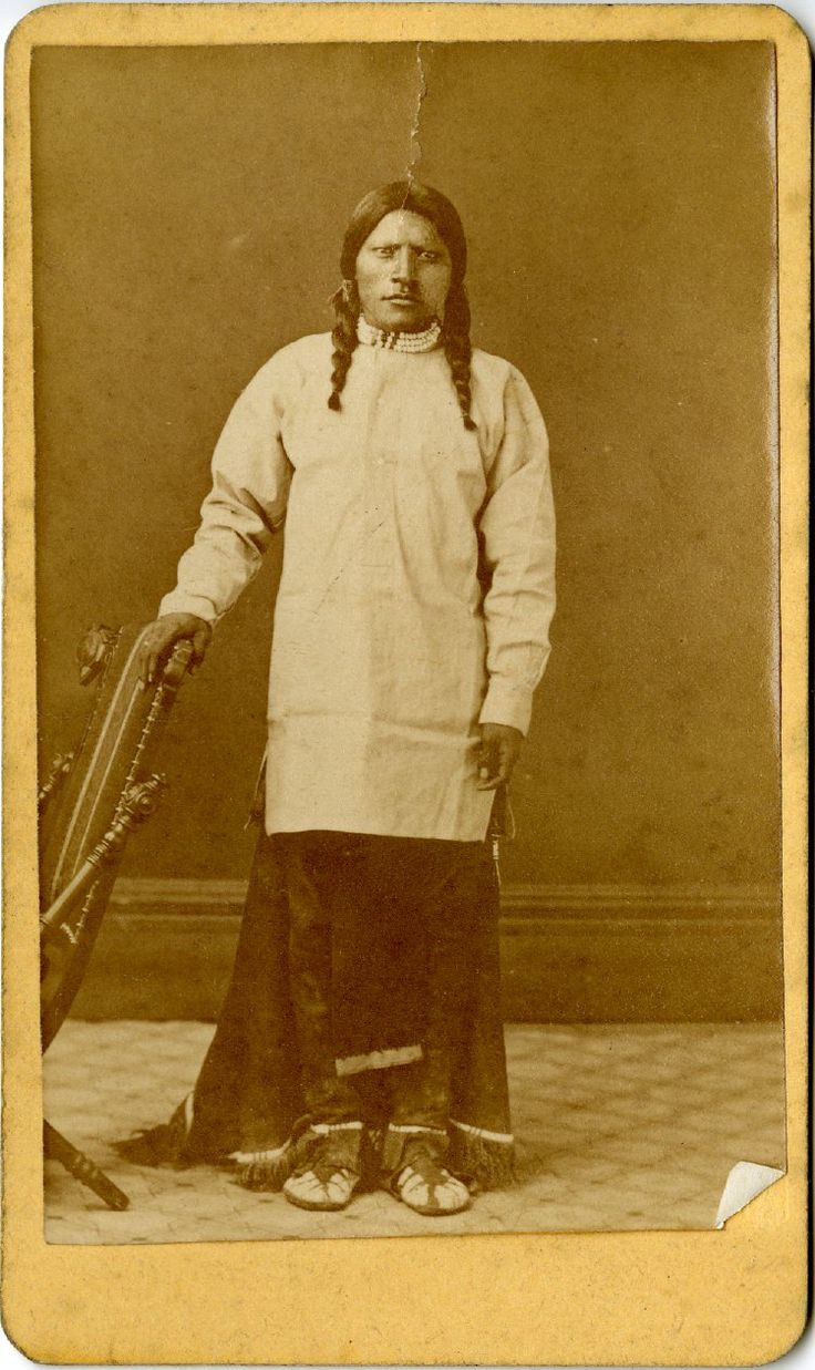 Studio Portrait Of A Native North America American Man, Standing Wearing A Cloth Tunic, A Hide Skirt, Moccasins, And A Beaded Choker; His Hair Is In Plaits And He Is Leaning On A Chair; Denver, United States Of America Albumen Print.