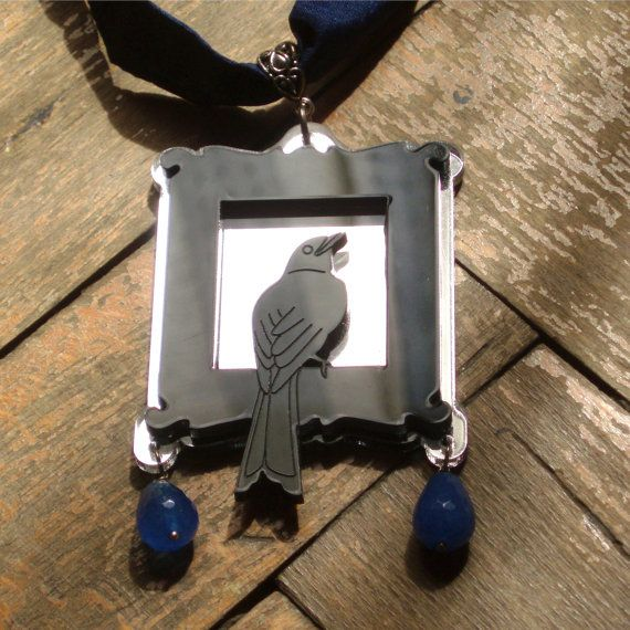 Necklace with a black bird in a frame medallion and blue silk ribbon
