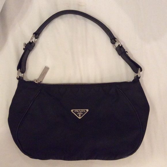 Prada small black purse I cannot confirm if its authentic. Tried looking for a serial number and it doesn't have one. The lining inside has the prada lodo all over, but the stitching has become undone on some parts. Outside the bag looks great!  Prada Bags