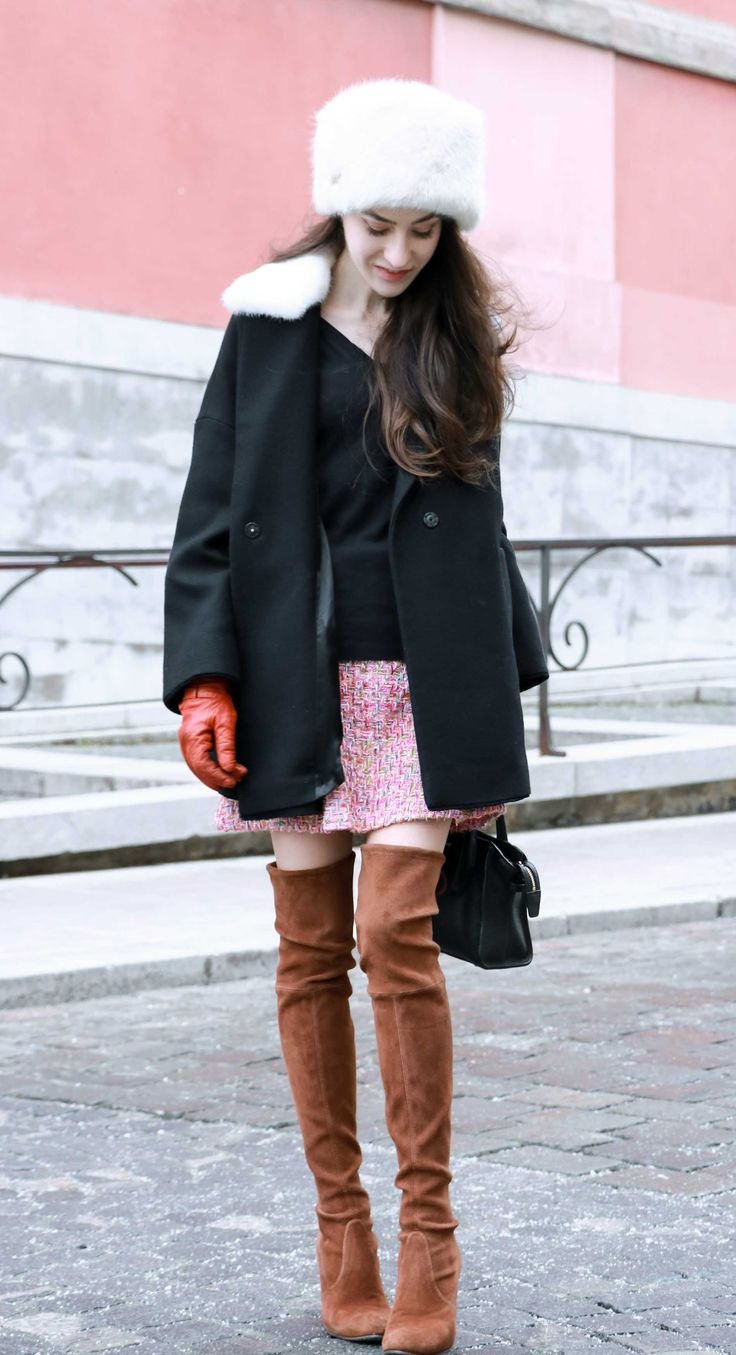 Fashion Blogger Veronika Lipar of Brunette from Wall Street dressed in Barts faux fur hat, black and white Escape short coat, mini velvet skirt from Storets, brown Stuart Weitzman over the knee boots on the streets of Ljubljana in winter