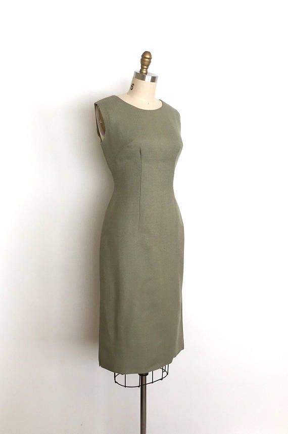 Elegant 50s wool wiggle dress. This dress features a beautiful subdued sage green colour and a timeless silhouette. Fitted sleeveless bodice, fitted waist and a straight wiggle skirt. Back metal zipper and the dress is fully lined.