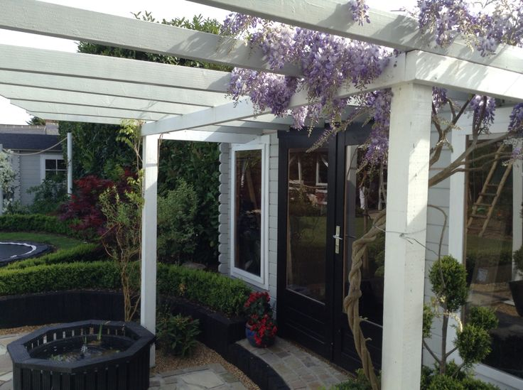 DIY grey pergola with trailing wisteria