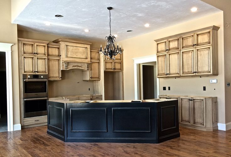 Frameless, full overlay cream-colored cabinets, with a dark brown glaze.