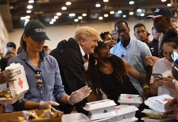Melania Trump Photos Photos - US President Donald Trump and First Lady Melania Trump serve food to Hurricane Harvey victims at NRG Center in Houston on September 2, 2017. / AFP PHOTO / Nicholas Kamm - Trump Arrives in Houston Area in Aftermath of Hurricane Harvey