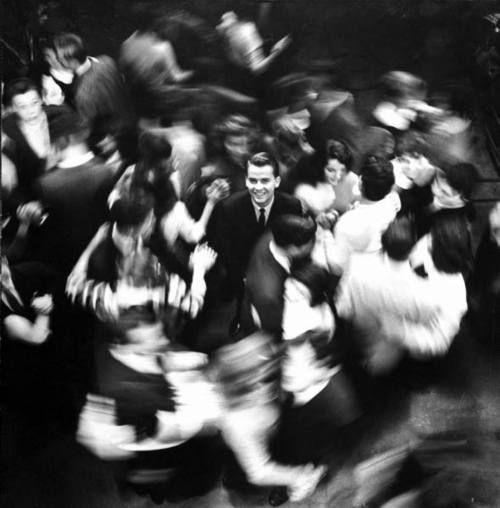 Dick Clark surrounded by a sea of dancing teenagers on American Bandstand