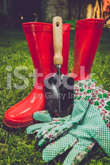 toned filter of garden tools and red boots on meadow royalty-free stock photo