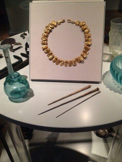 Kaptafel met luxe toiletartikelen: sieraden (ringen), spiegel, parfumflesjes, badoliepotje en strigiles (huidschrapertjes). Men smeerde zich na het baden in met olie en schraapte het er later af met een strigile.