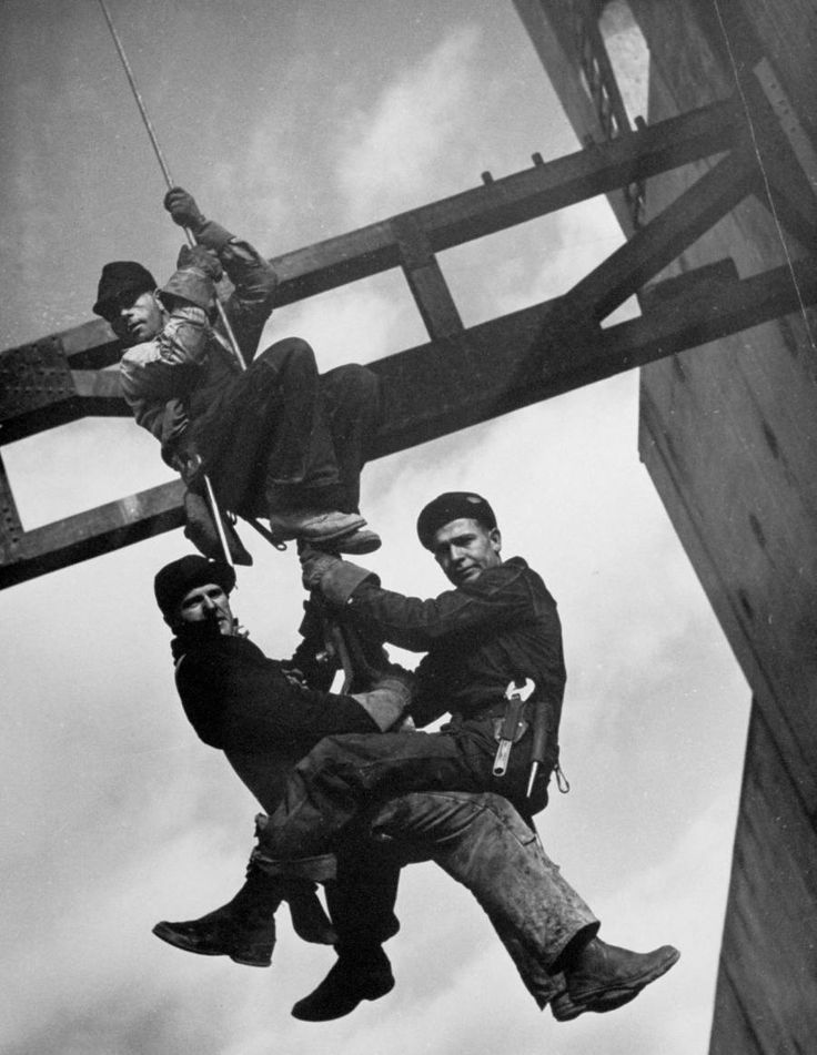 Relief Workers Hanging from Cable in Front of a Giant Beam During the Construction of Fort Peck Dam. Margaret Bourke-White. 1936