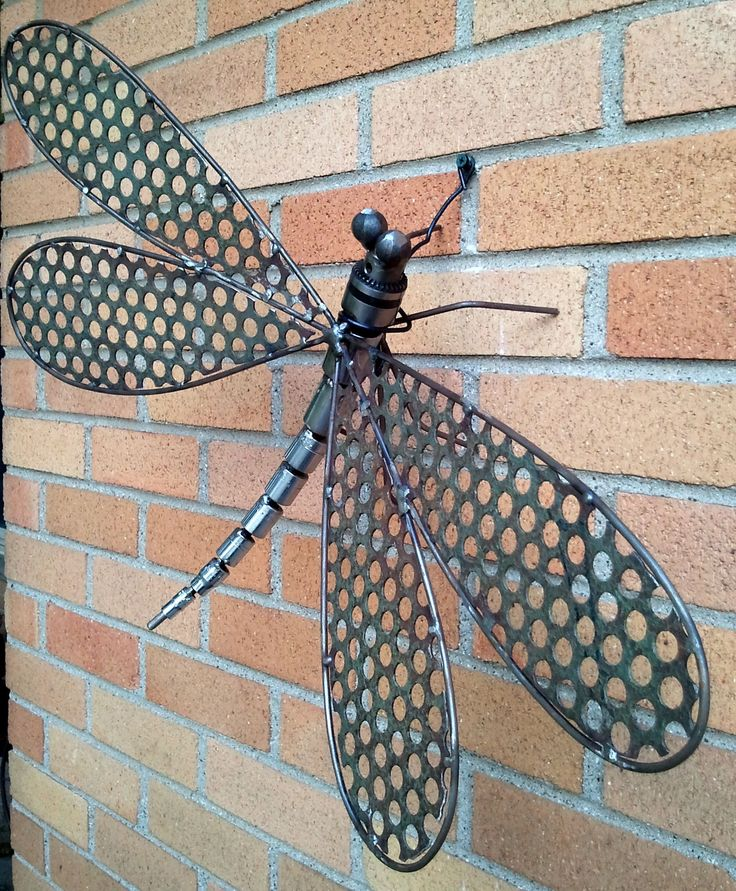Dragonfly sculpture skillfully welded out of reclaimed metal.  The head is from a drill chuck, wings from expanded metal and rod, the body  out of a mechanics socket set, legs from rod and the eyes are hammered steel balls. This one of a kind dragon fly would look beautiful in your garden, on a wall or in your home.