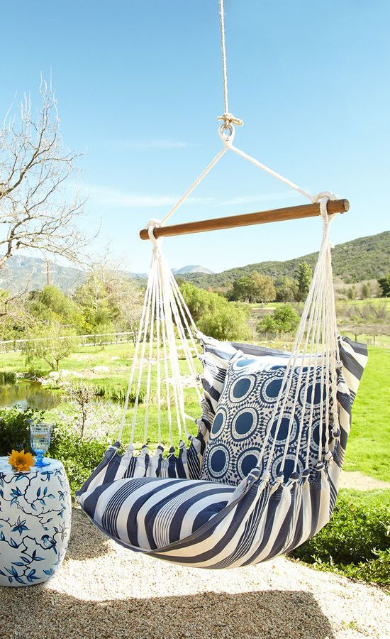 Handcrafted indoor/outdoor swinging chair with pillows.