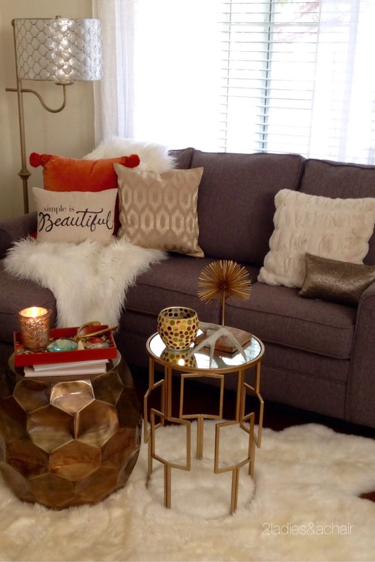 We couldn't resist this orange velvet pillow with pom-poms when we saw it at HomeGoods! It was the starting point for decorating this sofa for fall. We quickly paired it with a faux fur fluffy throw, then used neutral colors for the rest of the accessories. We added lots of gold and shine with these small tables from HomeGoods. Grouped together they are the perfect size for this sofa. They're also very functional since they can be easily moved and used elsewhere. Sponsored by HomeGoods