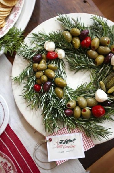 Clever winter holiday party wreath appetizer dish: plenty of fresh rosemary sprigs, olive mix, roasted cherry tomatoes or pickled little red peppers, small mozzarella balls.