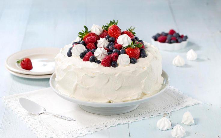 Ingenting sier fest mer enn en flott bløtkake. Denne er fylt med vaniljekrem, bringebærsyltetøy og banan og toppet med bær og pikekyss.