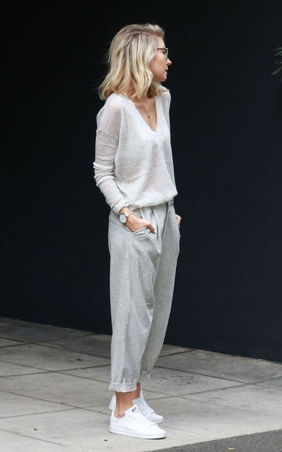 Lovely wispy light grays. Long sleeved v-neck translucent cashmere sweater in a color somewhere between white and gray paired with gray trouser style ankle grazer pants rolled to a cropped length. White sneakers. Watch, necklace, sunnies. Delicate, casual