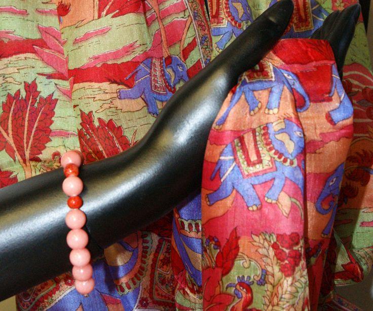 Armband van rhodrochrosiet en bamboe koraal. Zijden sjaal in warme rood-oranje kleur. www.sewiso.com