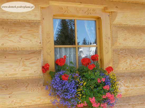 Okno domku ozdobione kwiatami