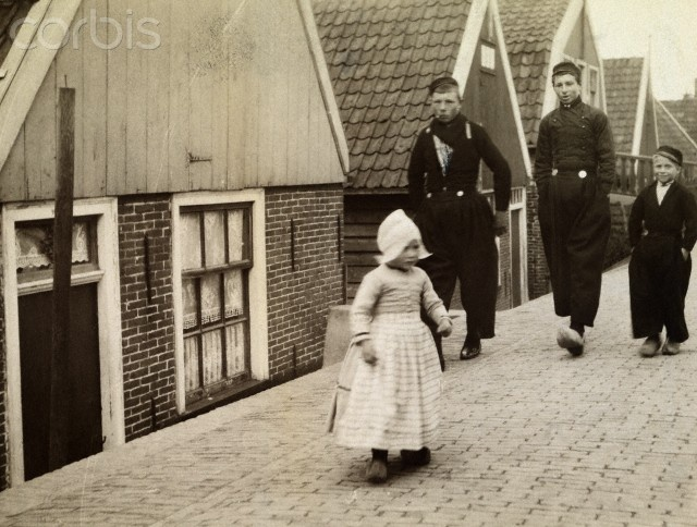 12-11-11 People walk a promenade that runs parallel to houses below sea level. 1915