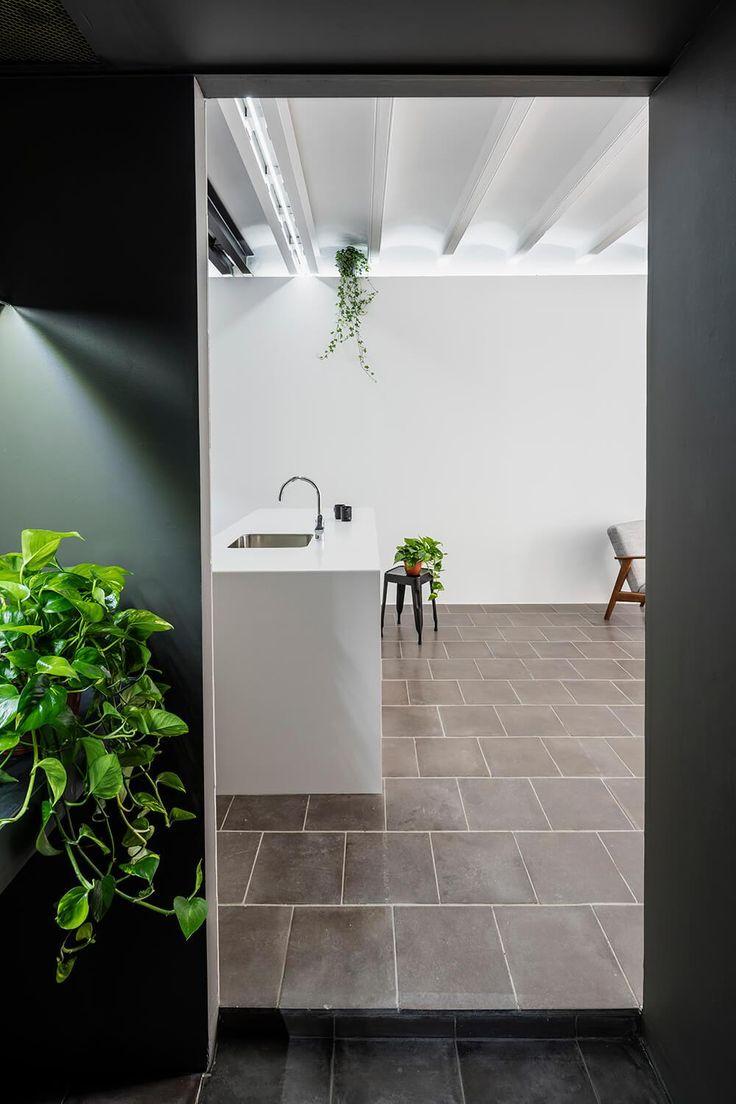 Hall com pintura escura, bancada com plantas. Apartamento Minimalista em Barcelona por RAS Studio